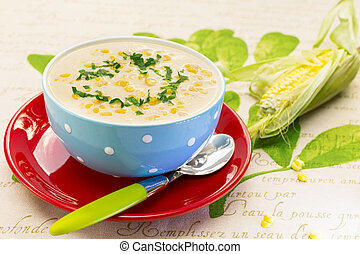 Cream of corn soup in blue bowl with fresh cob of corn on...