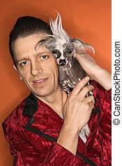 Man holding Chinese Crested dog - Caucasian mid-adult male...