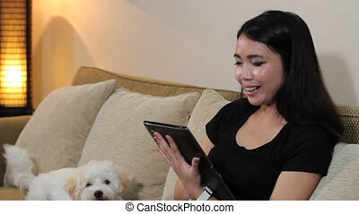 Asian Woman Talks On Tablet - A cute Asian woman talks to...