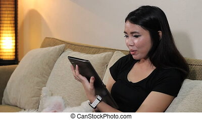 Asian Woman Talking On Tablet - A pretty Asian woman enjoys...
