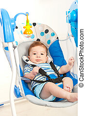 Baby boy in swing - Baby boy in a musical swing home against...
