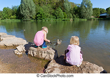 Two small girls feeding ducks on a lake squatting down on...