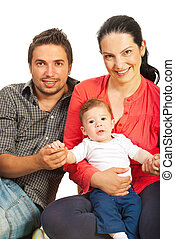 Happy family sitting on floor and mother holding baby boy...
