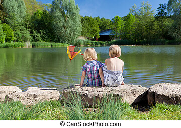 Two little girls fishing at the lake - Rear view of two...