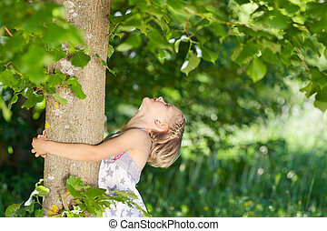 Young girl hugging a tree trunk while looking up into the...