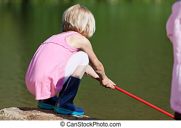 Little girl fishing with a net - Little girl bending down at...