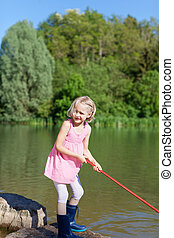 Pretty little girl fishing at the lake standing on the rocky...