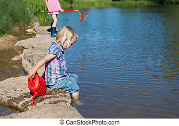 Little girl paddling her feet in the lake - Adorable little...