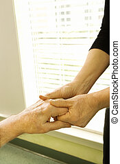 Woman holding mature woman\'s hand.