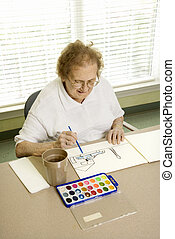 Mature woman painting.