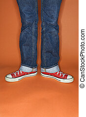 Feet turned outward. - Person in jeans and sneakers with...