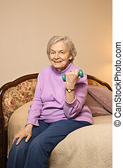 Mature woman lifting weight. - Elderly Caucasian woman in...