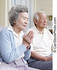 senior asian couple praying.