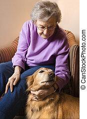 Mature woman petting dog.