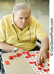 Mature Caucasian playing bingo - Elderly Caucasian man...