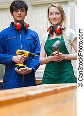 Two woodworking students standing before a workbench -...