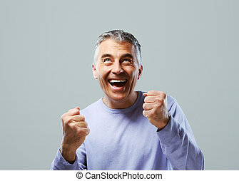 Winner - Portrait of excited mature man, raising his fists...