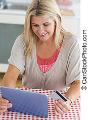 Woman shopping online with her tablet pc - Happy woman...
