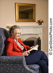 Elderly woman reading book.
