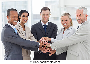 Group of business people piling up their hands together in...