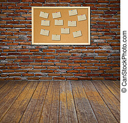 Cork bulletin board with old paper note on brick wall