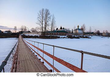 Suspension foot bridge over the frozen river