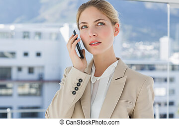 Serious businesswoman holding her phone