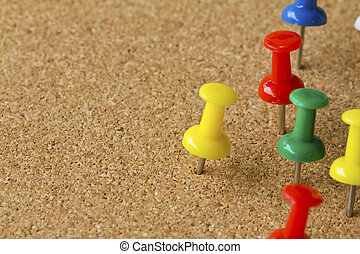 Group of colorful push pins on cork bulletin board
