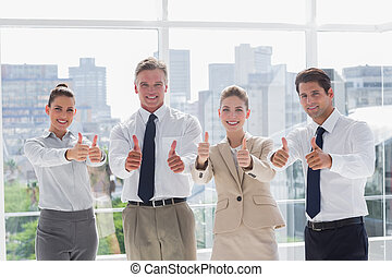 Smiling team of business people giving thumbs up in the...