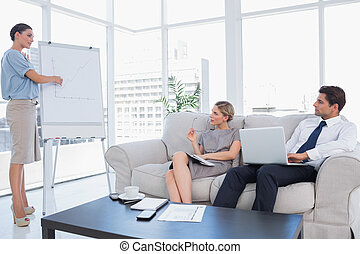 Business woman presenting something on a whiteboard to her...