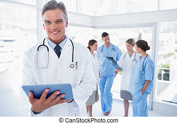 Smiling doctor holding digital tablet in front of his...