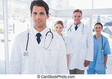 Attractive doctor in front of his team - Attractive doctor...