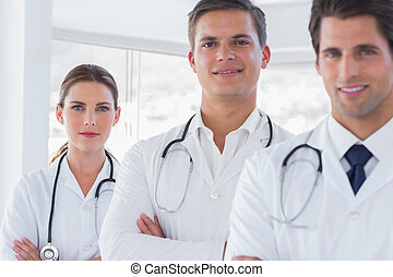 Three smiling doctors with lab coats - Three smiling doctors...