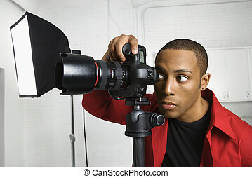 Photographer looking through camera. - African American...