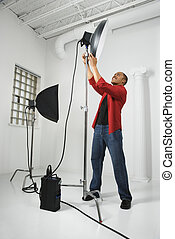 Man adjusting studio lights. - African American young male...