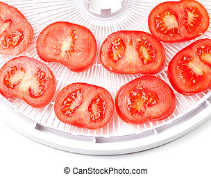 Ripe tomato on food dehydrator tray, ready to dry On white...