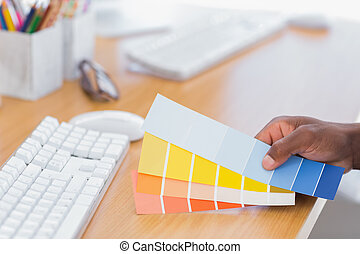 Interior designer holding colour charts in a modern office