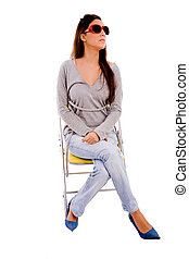 front view of young female sitting on chair against white...