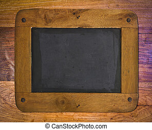 Old blackboard with a wooden frame on wood wall.