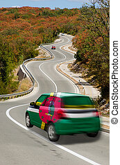 Car on road in national flag of dominica colors - traveling...