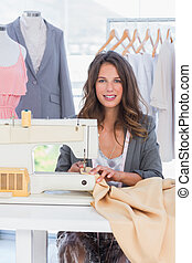 Fashion designer sewing textile and smiling to the camera