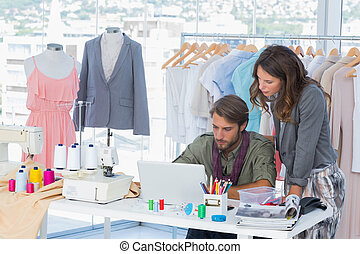 Two fashion designers working on laptop
