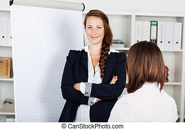 Confident business woman with a flip chart