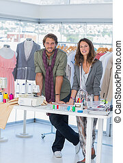 Two fashion designers standing in a bright creative office -...
