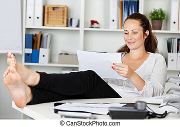 Relaxing woman sitting while reading inside the office