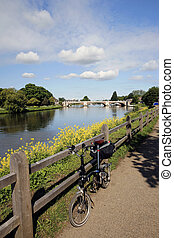 Folding bicycle stands alone near River Thames, Hampton...