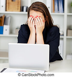 Tired or depressed businesswoman sitting at her desk behind...