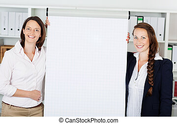 Businesswomen giving a flip chart presentation - Two...