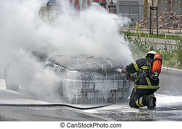 Firefighter is putting out a burning car - Burning motor...