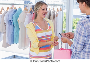 Cashier giving credit card to customer in a bright shop